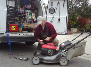 Man servicing a honda lawn mower behind a white van Whats included in a lawn mower service